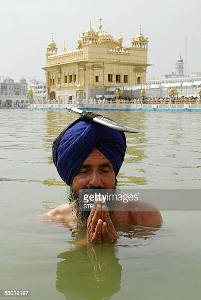 An Indian Sikh devotee takes a holy dip in the sarover and pays homage in the front of the Shri Akal Takhat Sahihib in front of the Golden temple in...