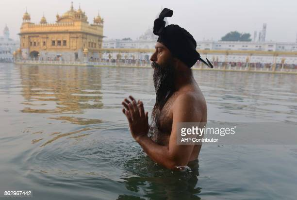 An Indian Sikh devotee takes an early morning dip in the holy water tank 'sarovar' during Diwali Festival at the illuminated Golden Temple in...