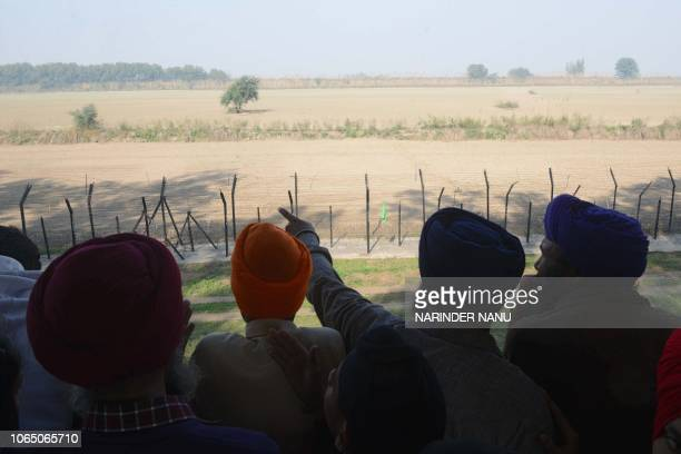 An Indian Sikh devotees look out towards the Gurdwara Kartarpur Sahib which is situated in Pakistan from Indian side at Dera Baba Nanak on the...