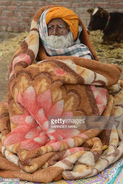 An Indian Sikh elder Bawa Singh covers himself with a blanket to keep warm at Vallah village on the outskirts of Amritsar on December 14 2012 AFP...