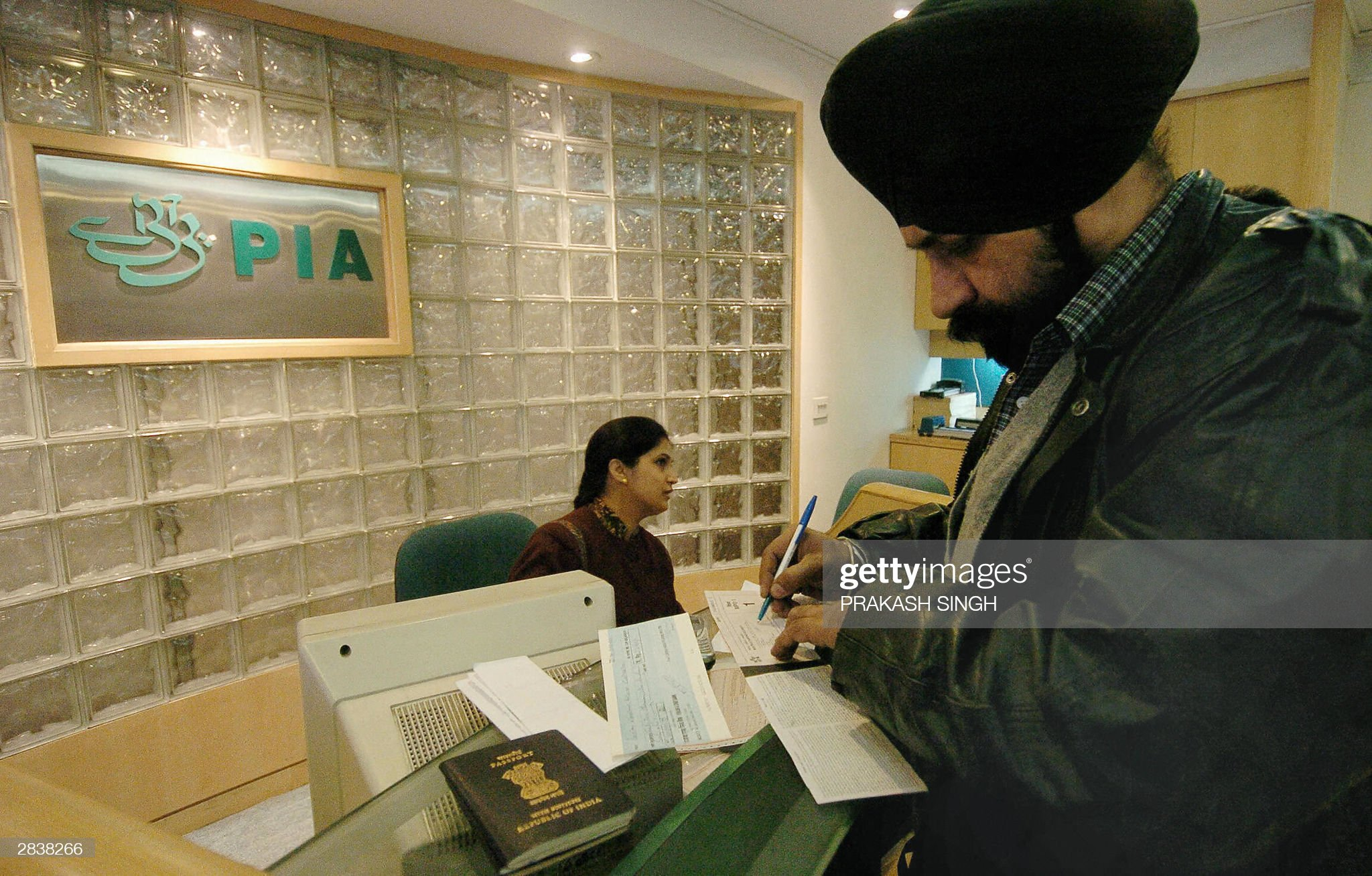 An Indian Sikh man(L) fills out a form w : News Photo