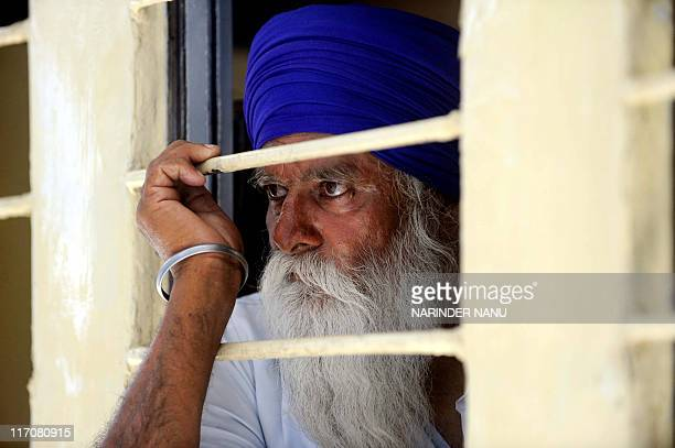 An Indian Sikh pilgrim looks on after boarding a train for Pakistan at railway station in Amritsar on June 21 2011 Hundreds of Indian Sikh pilgrims...