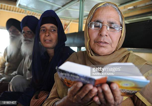 An Indian Sikh pilgrim reads a Holy Book after boarding a train bound for Pakistan at a railway station in Amritsar on November 8 2011 Thousands of...