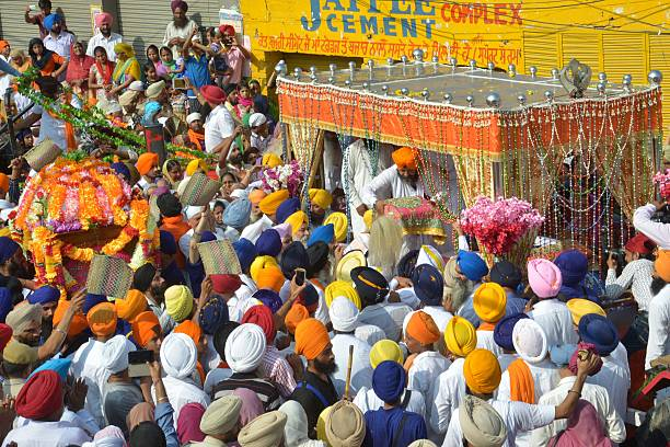 An Indian Sikh priest places the Sikh holy book the Guru Granth Sahib onto a palanquin during a procession for Sikh Holy figure Guru Nanak Dev`s...