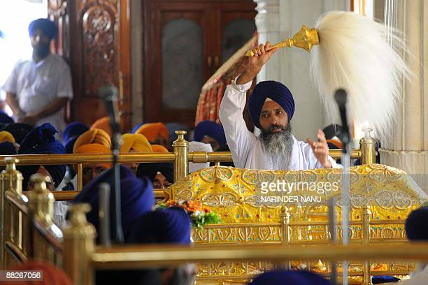 An Indian Sikh priest sits behind The Guru Granth Sahib at The Sri Akal Takht in The Golden Temple in Amritsar on June 6 on the occassion of...
