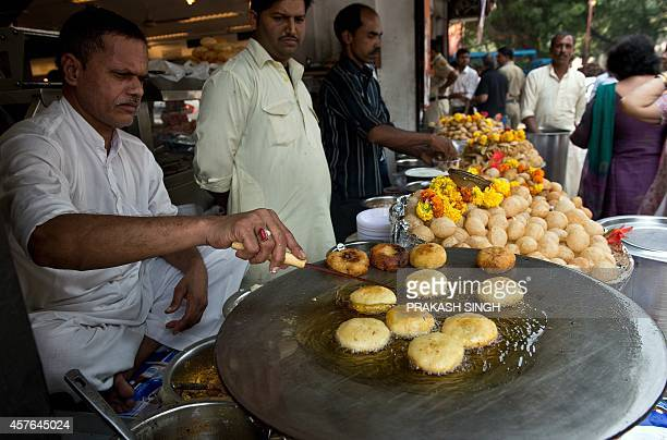 An Indian snacks vendor cooks alootikki at a roadside shop in New Delhi on October 22 2014 AFP PHOTO / PRAKASH SINGH