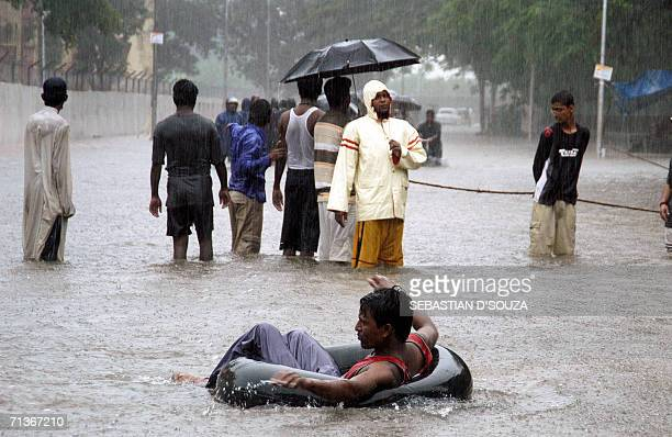 An Indian social worker sits on a lifebuoy as others stand ready for rescue outside the Air India colony as heavy rains lashed India's financial hub...