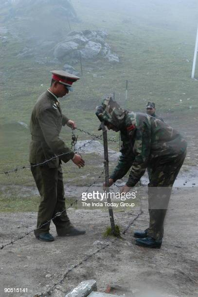 An Indian soldier and a Chinese soldier remove barbed wire on the border fence at Nathu La to allow commanders of both sides to meet for a flag...