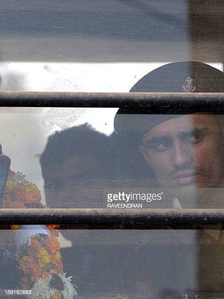 An Indian soldier holding a wreath looks on from inside a military truck as he waits for the arrival of the bodies of two comrades allegedly killed...