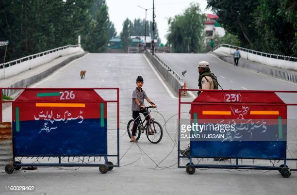 An Indian soldier patrols on a deserted street as a child looks on during curfew in Srinagar on August 6 2019 India's home affairs minister on August...