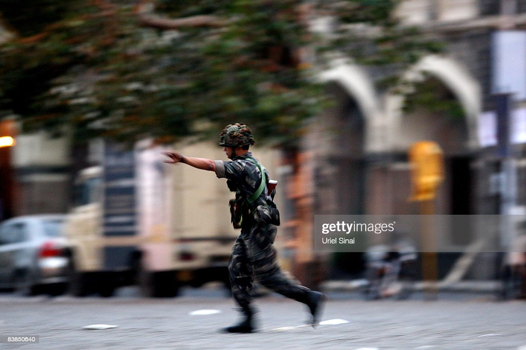 An Indian soldier runs for cover outside the Taj Mahal Palace & Tower Hotel during an armed siege, on November 28, 2008 in Mumbai, India. The city of Mumbai was rocked by multiple coordinated terrorist attacks that targeted locations popular with foreigners, late on the night of November 26 and into the next morning, killing scores and wounding hundreds in shootings and blasts around the city