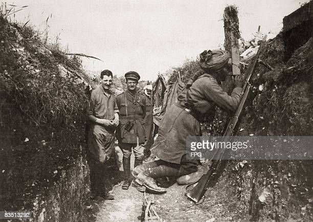 An Indian soldier serving with the British Army keeps watch on the German trenches using a periscope circa 1916