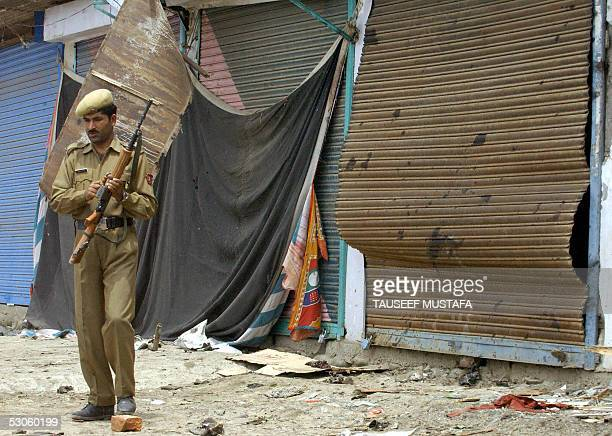 An Indian soldier stands alert in front of a row of damaged shops after a bomb blast in Pulwama some 30kms south of Srinagar 13 June 2005 At least...