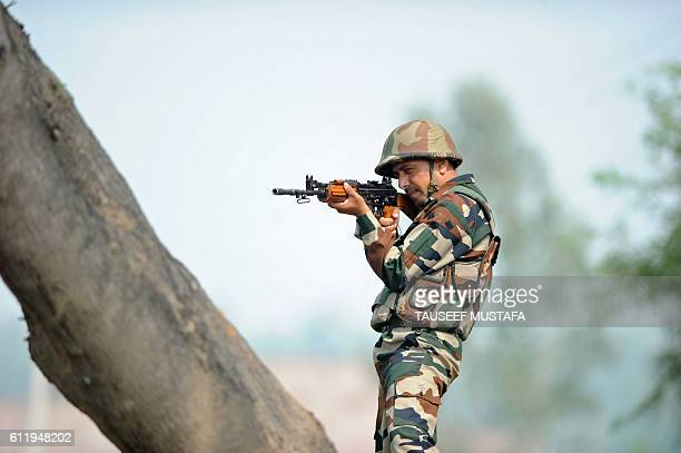An Indian soldier takes up position at an outpost at the IndiaPakistan border in RS Pora southwest of Jammu on October 2 2016 India has evacuated...