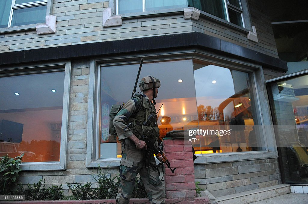 An Indian solider stands guard outside a hotel after a shooting incident at a hotel on the outskirts of Srinagar on October 19,2012. At least three gunmen attacked a hotel in the restive region of Indian Kashmir, killing a bellboy and leaving at least two other people injured, security forces said. The armed gang began shooting outside the Silver Star hotel on the outskirts of the main city of Srinagar at about 4:30 pm (1100 GMT) before entering the premises and firing 'indiscriminately,' according to a police statement. AFP PHOTO/ Rouf BHAT