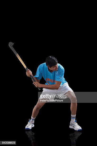 An Indian sportsman practicing hockey isolated over black background