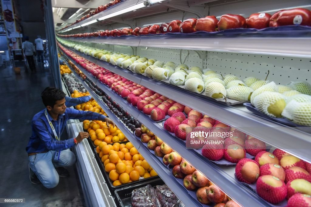 An Indian staff member arranges fruit at a newly launched