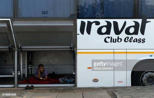 An Indian state transportation employee rests inside a bus luggage compartment at a bus terminal in Chennai on February 16 2018 India suffers severe...