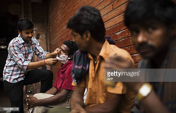 An Indian street barber shaves a customer as two men drink tea in the Old Quarters of New Delhi on May 12 2013 The Indian government forecasts the...