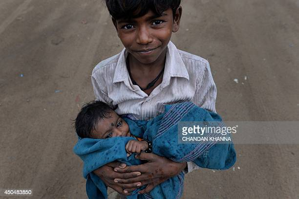 An Indian street child poses with his sister in his arms as raindrops began falling in New Delhi on June 12 2014 Rain fell in the Indian capital...