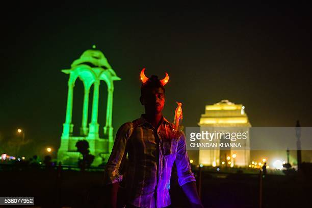 TOPSHOT An Indian street vendor sells toys next to the Empty Canopy structure near India Gate as it is lit green to support planting trees and going...