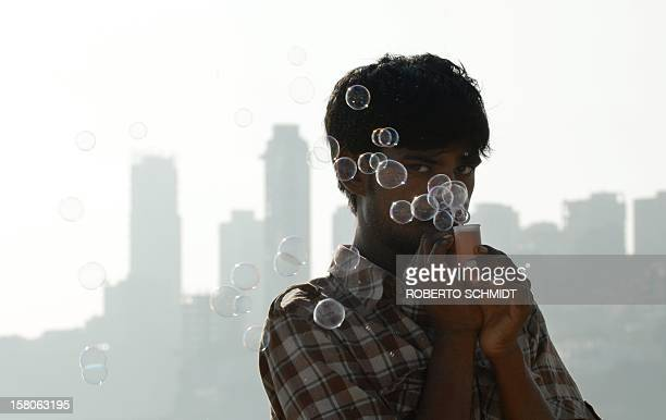 An Indian street vendor who called himself Tun Tun and makes a living by selling soap bubbles stands on a popular beach near high rises in South...