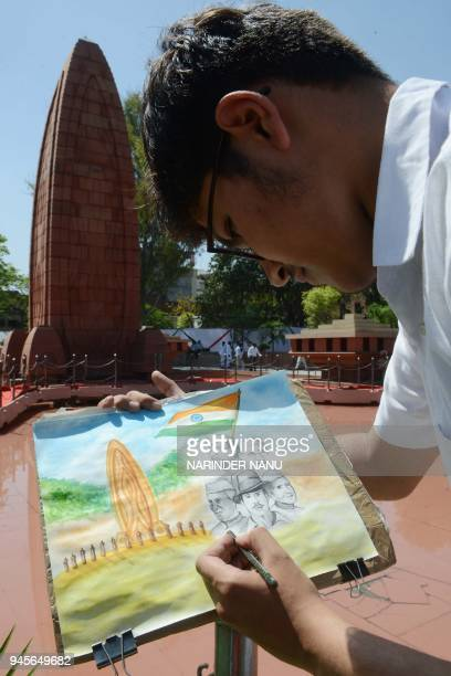 An Indian student draw a painting of the Flame of Liberty along with Indian freedom fighter Shaheed Bhagat Singh during the 99th anniversary of the...