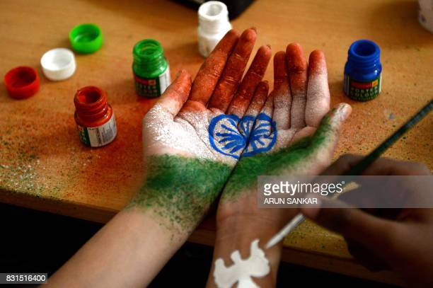 An Indian student gets their hand painted with the Indian national flag at an event during Indian Independence Day celebrations in Chennai on August...