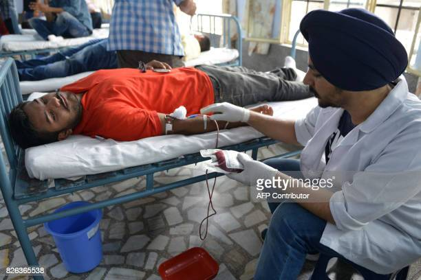 An Indian student gives blood during a blood donation camp to mark the 25th anniversary of the death of humanist and philanthropist Bhagat Puran...