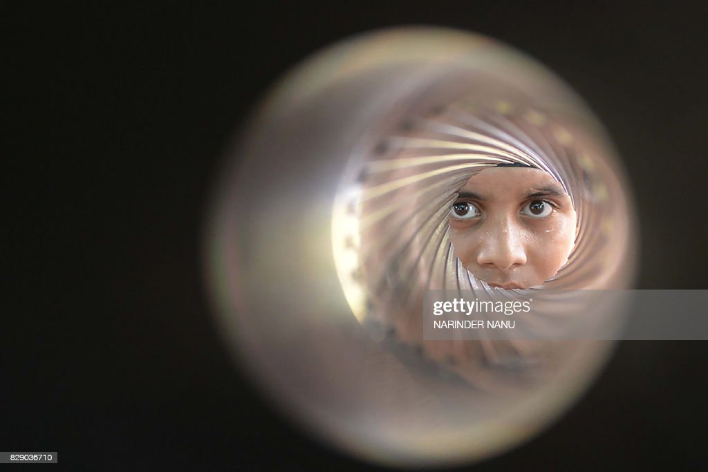 TOPSHOT An Indian student poses as he looks down the barrel of an 84MM rocket launcher during an Indian Army exhibition at Panther Stadium in...