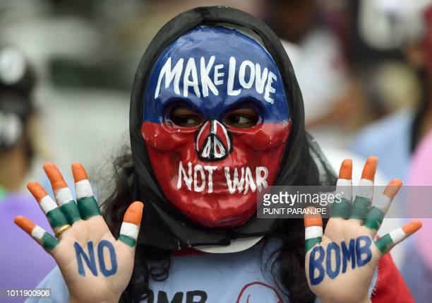 TOPSHOT An Indian student wearing a mask poses with her hands painted with a slogans for peace during a rally to mark Hiroshima Day in Mumbai on...