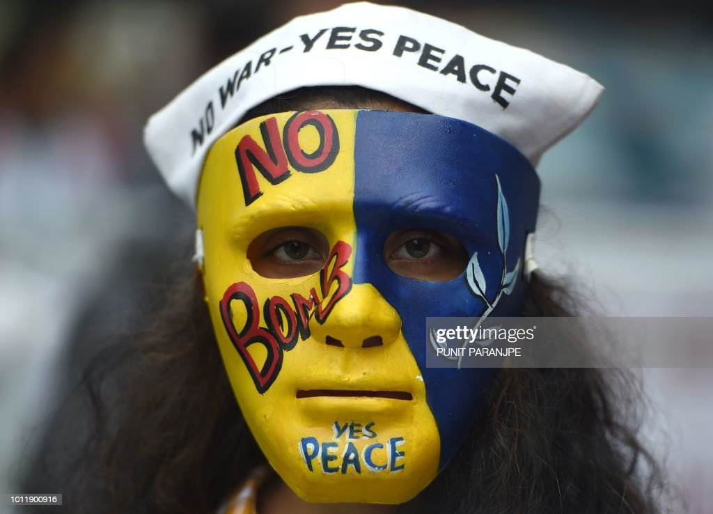 An Indian student wears a mask with slogans for peace during a rally
