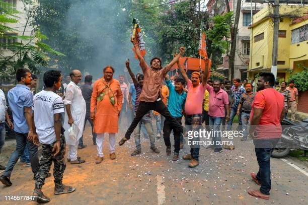 An Indian supporter of Bharatiya Janata Party jumps in the air as he celebrates along with others on the vote results day for India's general...