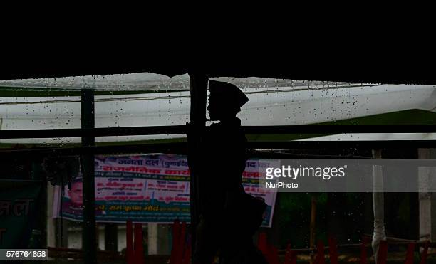 An indian supporter of janta Dal united JD listens to the sppeech of Bihar's Chief Minister Nitish Kumar's speech during heavy rainsin the divisional...