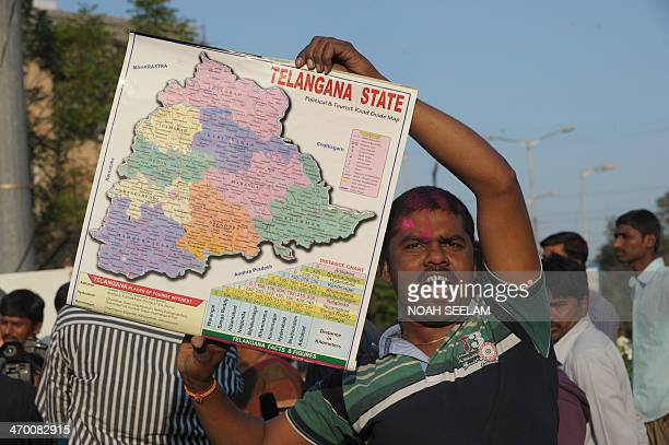 An Indian supporter of Telangana Rastra Samithi party holds a map as he celebrates the planned creation of Telangana state in Hyderabad on February...