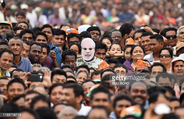 An Indian supporter of the Bharatiya Janata Party wearing a mask of Prime Minister Narendra Modi along with other supporters attend one of Modi's...