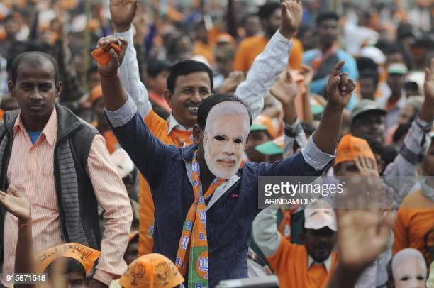 An Indian supporter of the Bharatiya Janata Party wearing a mask with Indian Prime minister Narendra Modi's picture gestures as Modi speaks during a...
