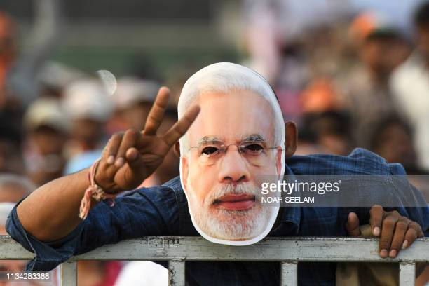 An Indian supporter of the Bharatiya Janata Party wears a mask of Prime Minister Narendra Modi as he attends a meeting of his political campaign...
