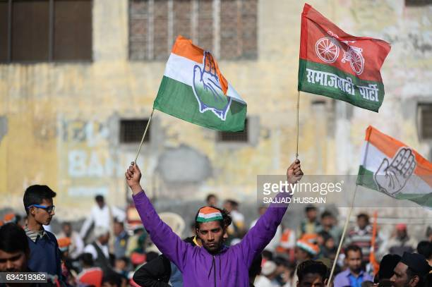 An Indian supporter of the Congress and Samajwadi political parties waves the flags of both during an election rally by Congress Party leader Rahul...