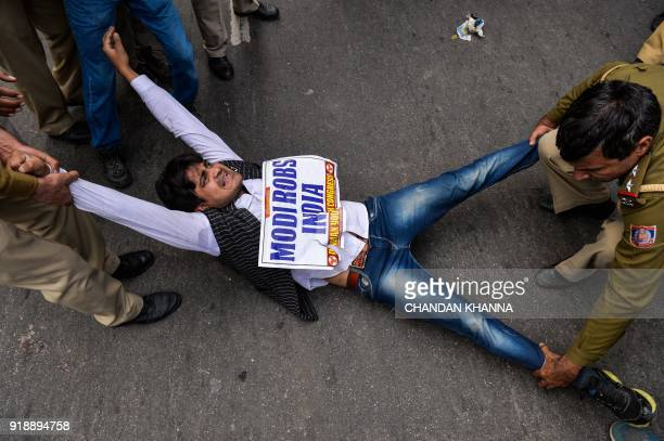 TOPSHOT An Indian supporter of the Congress Party shout slogans as police detain him during a protest against billionaire jeweller Nirav Modi in New...
