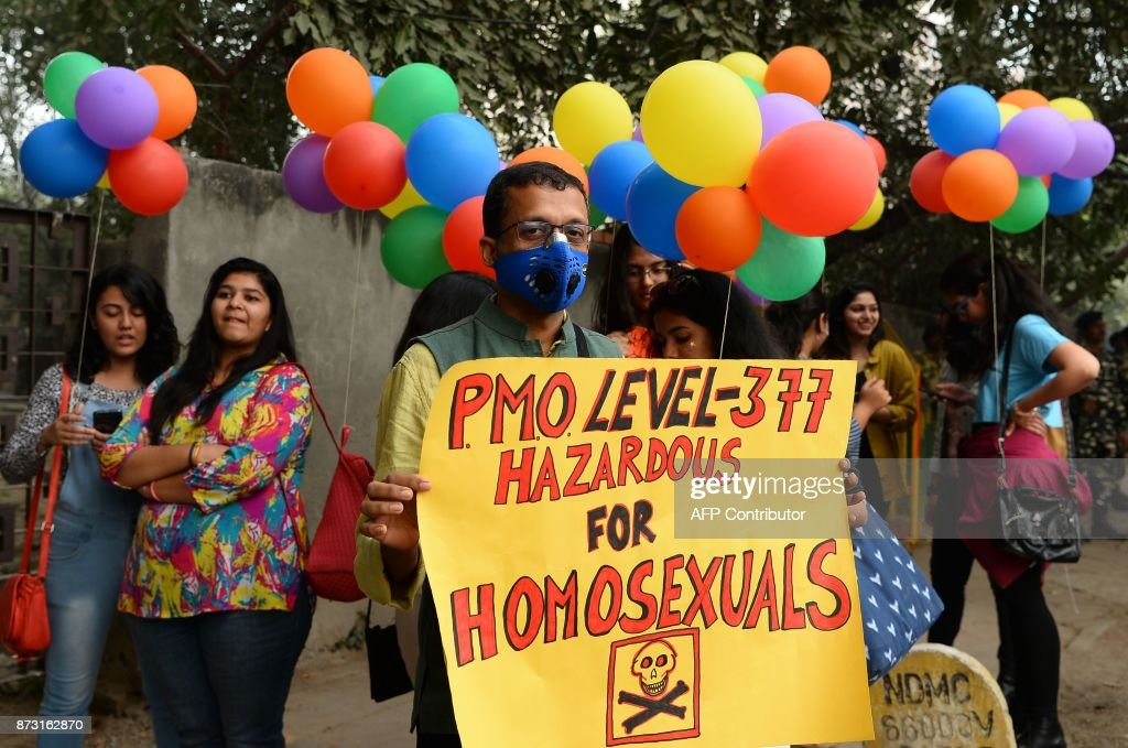 An Indian supporter of the lesbian, gay, bisexual, transgender (LGBT) community wearing a pollution mask hold a placard as he takes part in a pride parade in New Delhi on November 12, 2017. Hundreds of members of the LGBT community marched through the Indian capital for the 10th annual Delhi Queer Pride Parade. HUSSAIN