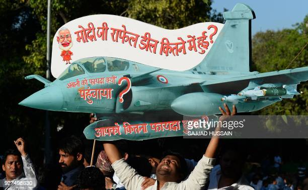 An Indian supporter of the opposition Indian National Congress party holds a model of Rafale fighter jet as he shouts slogans during a protest...