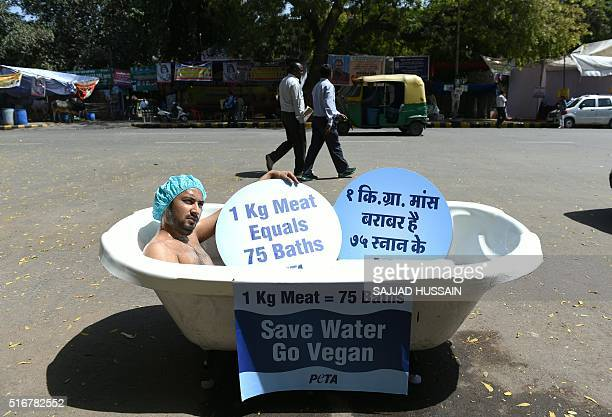 An Indian supporter of the People for the Ethical Treatment of Animals organisation bathes publicly in a bathtub at a roadside during a protest held...
