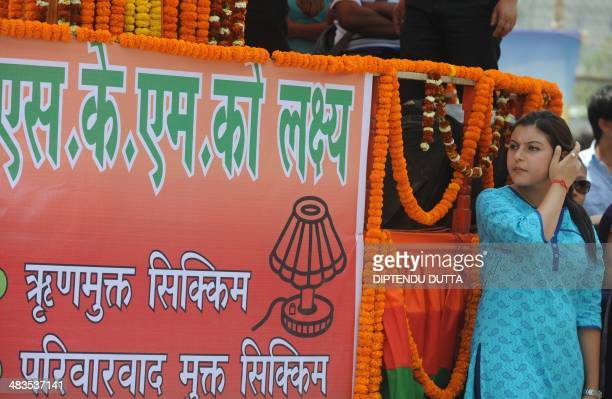 An Indian supporter stands near a banner of Sikkim Krantikari Morcha party as she listens to the speech of supremo Prem Singh Golay the main...