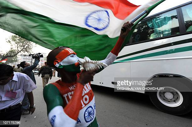 An Indian supporter waves a national flag to welcome the team passing by in a bus to play their first oneday international cricket match against New...