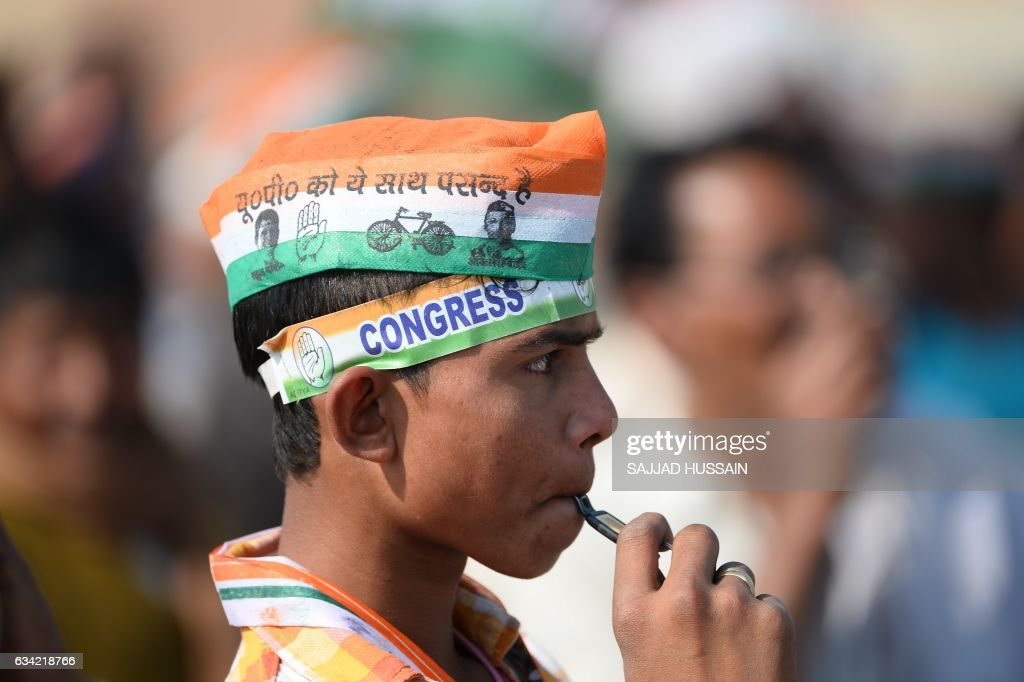 An Indian supporter wears a hat bearing images of the Congress political party during an election rally by Congress Party leader Rahul Gandhi ahead...