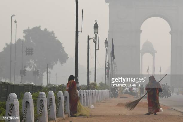 An Indian sweeper cleans a road amid heavy smog near India Gate in New Delhi on November 16 2017 Delhi is now the world's most polluted capital...