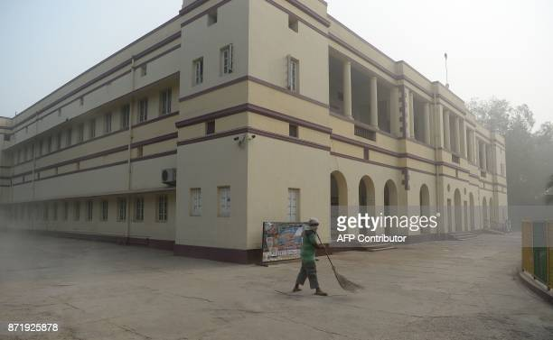 An Indian sweeper cleans the courtyard of a closed school amid heavy smog in New Delhi on November 9 2017 Schools closed across large swathes of...