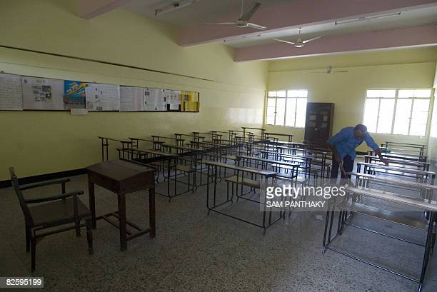 An Indian sweeper sweeps an empty classroom of Mount Carmel High School in Ahmedabad on August 29 as the school closed in a show of solidarity with...