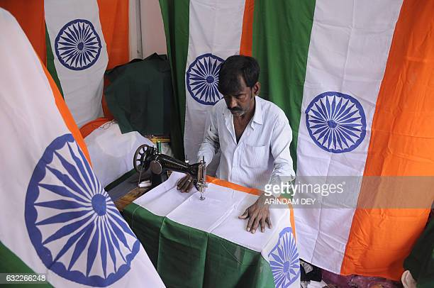 An Indian tailor stitches a national tricolour flag ahead of India's 68th Republic Day celebration at a shop in Agartala capital of northeastern...